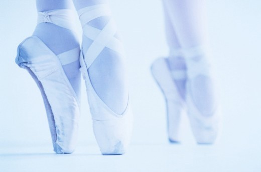 tungsten close-up of two female ballet dancers standing on their toes : Stock Photo