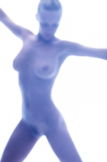 blurred shot of a nude woman posing with her arms held out (tungsten) : Stock Photo
