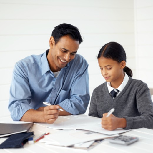Stock Photo: 1491R-124171 Young man helping his teenage daughter with homework (11-13)