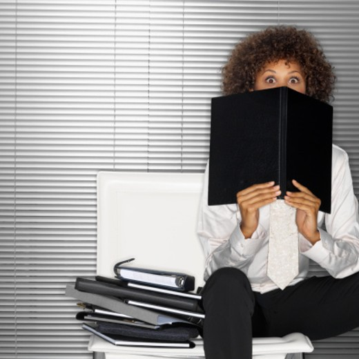 Stock Photo: 1491R-125645 Young businesswoman sitting on a chair looking over a folder