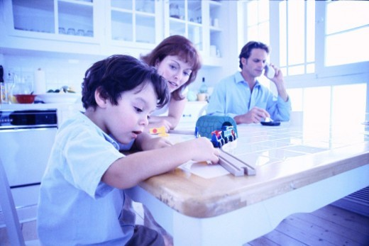 tungsten shot of a boy sitting with his parents at a table and playing with his toys : Stock Photo