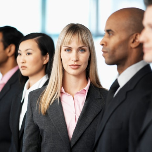 Close-up of a group of young executives standing in a single line : Stock Photo