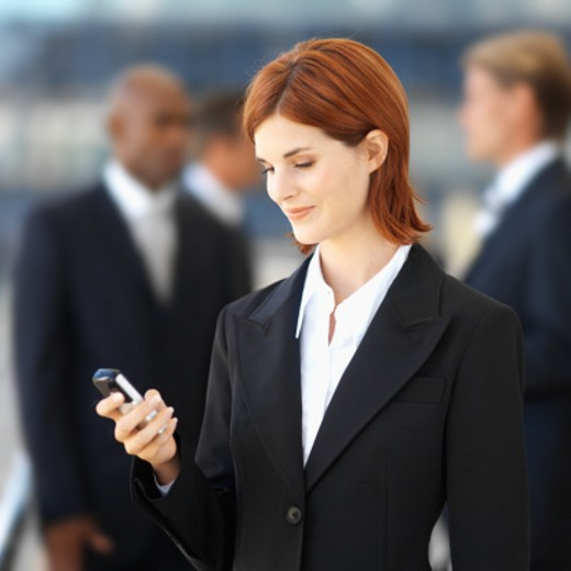 Stock Photo: 1491R-128314 Young businesswoman looking at a mobile phone
