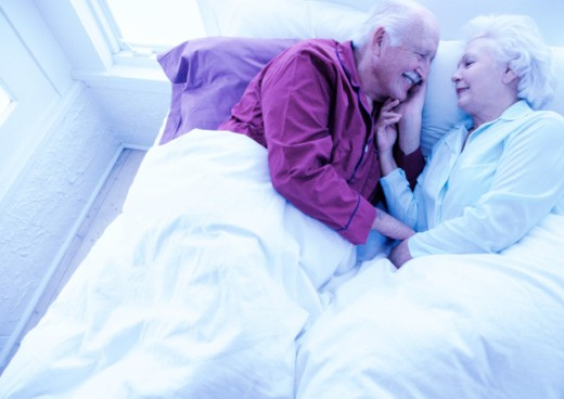 high angle view of a mature couple snuggling in bed; tungsten : Stock Photo