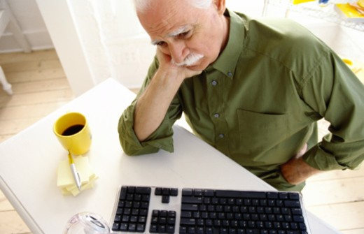 Stock Photo: 1491R-134040 high angle view of an elderly man sitting at a computer station