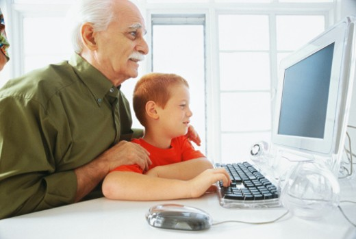Stock Photo: 1491R-134073 side profile of a boy (8-10) working on the computer with his grandfather standing behind him