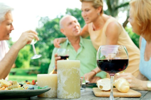 close-up of a wine glass and candles at an outdoor luncheon : Stock Photo