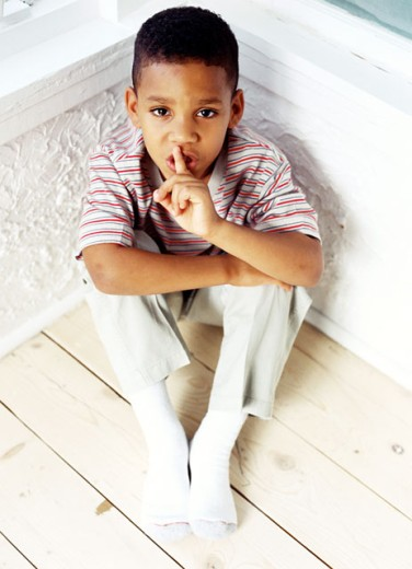 high angle view of a boy (8-10) sitting in a corner with a finger to his lips : Stock Photo
