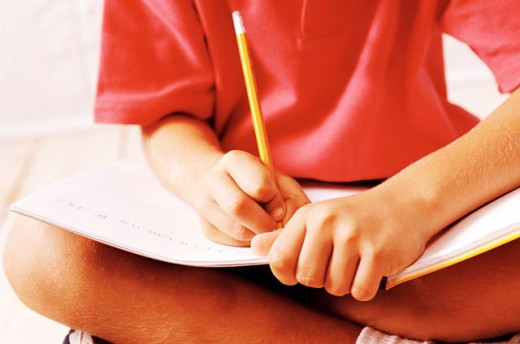 close up of a child's (8-10) hands writing in a notebook : Stock Photo
