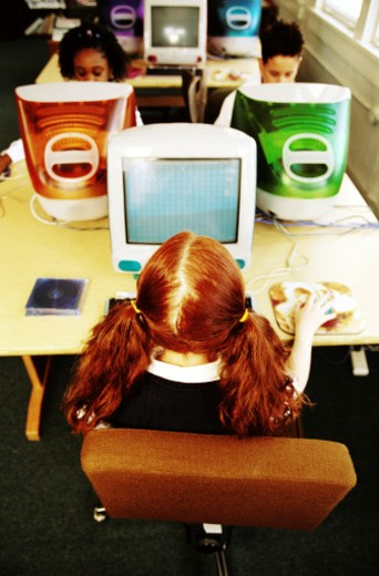 view from behind of a girl (8-10) sitting at a computer terminal in school : Stock Photo