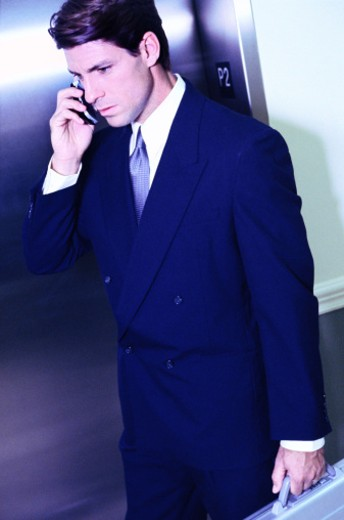 toned shot of a businessman talking on a mobile phone : Stock Photo