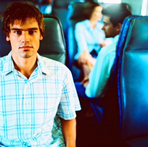 close-up of a young man sitting on the seat of a commuter train : Stock Photo