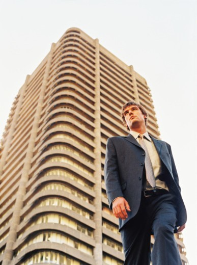 low angle view of a young businessman standing outside a city high rise : Stock Photo