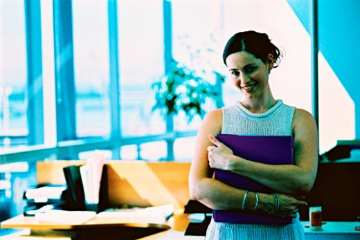 portrait of a woman standing hugging a folder and smiling : Stock Photo