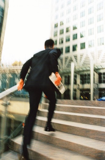 Stock Photo: 1491R-145047 blurred view from behind of a businessman running up the steps