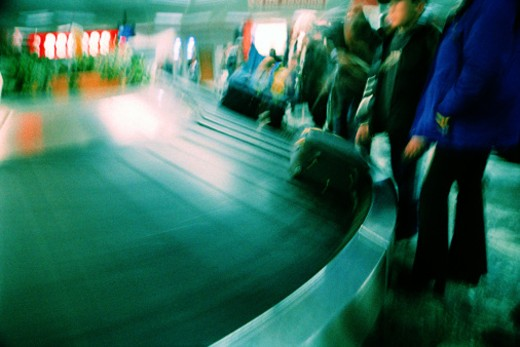 blurred shot of the legs of people waiting for luggage at an airport : Stock Photo