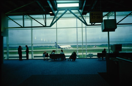 silhouette of people standing in an airports waiting lounge : Stock Photo