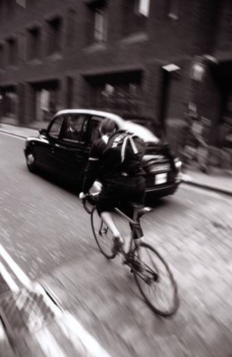 black and white view from behind of a man riding a cycle on the street : Stock Photo