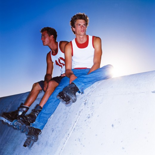 Stock Photo: 1491R-148088 low angle view of two young men sitting on a wall wearing roller skates