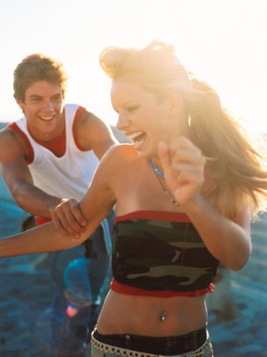 close-up of a young man playing catch with a young woman on the beach : Stock Photo