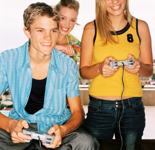 Stock Photo: 1491R-152026 close-up of a teenage boy playing video games with two teenage girls