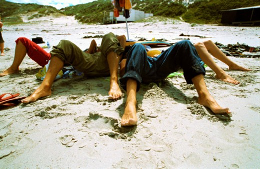 close-up of the feet of group of friends lying on the beach : Stock Photo