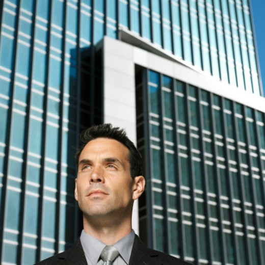 Young businessman standing with buildings in the background : Stock Photo