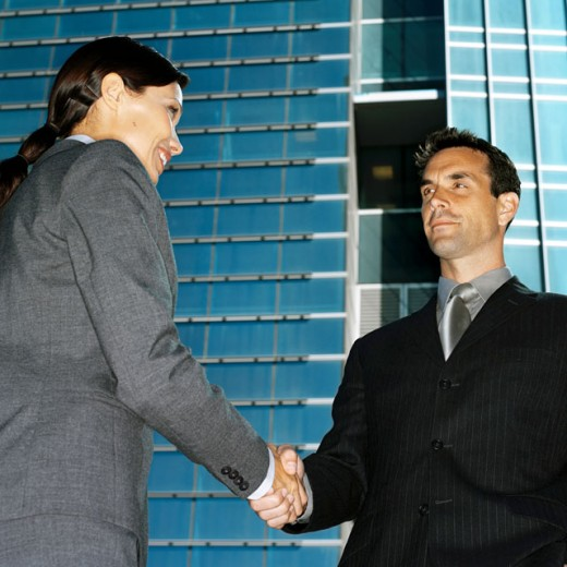 Low angle view of a young businessman and a young businesswoman shaking hands : Stock Photo