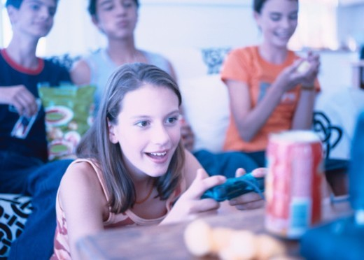 Stock Photo: 1491R-155047 a group of young teenagers playing video games and smiling (tungsten)