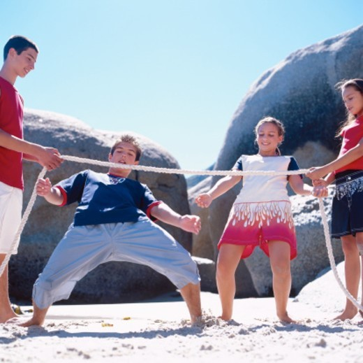 a group of young teenagers doing the limbo : Stock Photo
