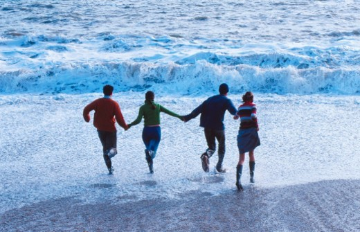 high angle view of two couples holding hands and running into the surf at the beach : Stock Photo