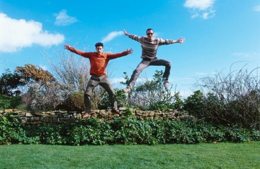 view of two young men leaping in the air in a garden : Stock Photo