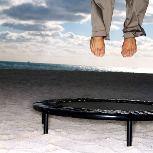 Person's feet in mid air over a trampoline : Stock Photo
