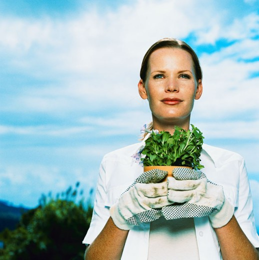 Stock Photo: 1491R-159046 portrait of a young woman with gloves holding a potted plant