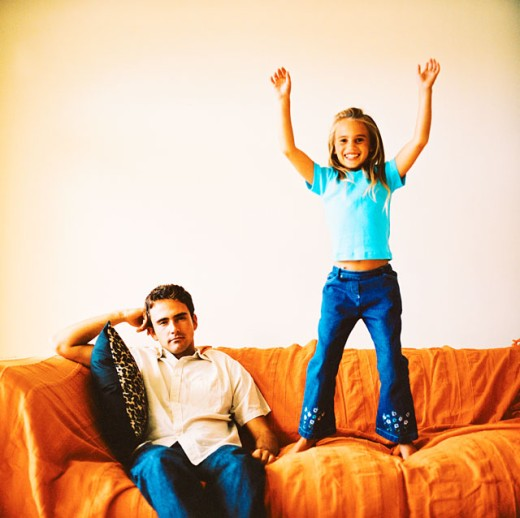 portrait of a young girl (8-10) standing on the couch and her father sitting next to her : Stock Photo