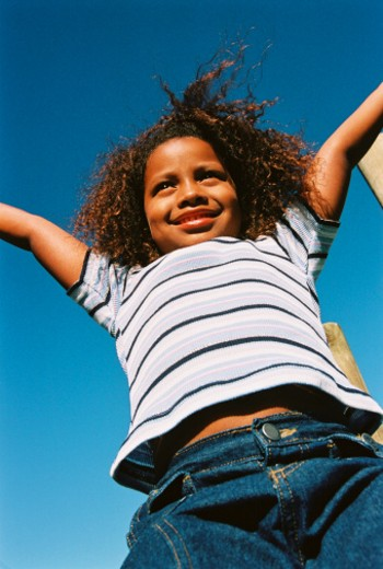 Stock Photo: 1491R-159238 portrait of a young girl (8-10) with her hands up in the air