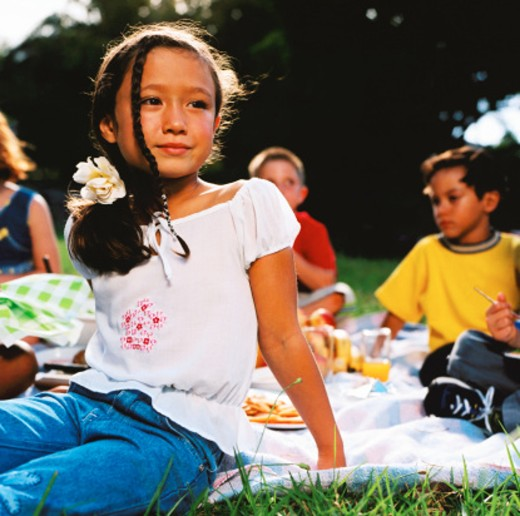 shot of a group of young children sitting on a lawn : Stock Photo