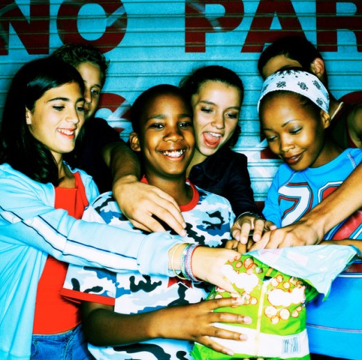 Stock Photo: 1491R-161051 view of a group of teenagers reaching into a bag of chips together; smiling