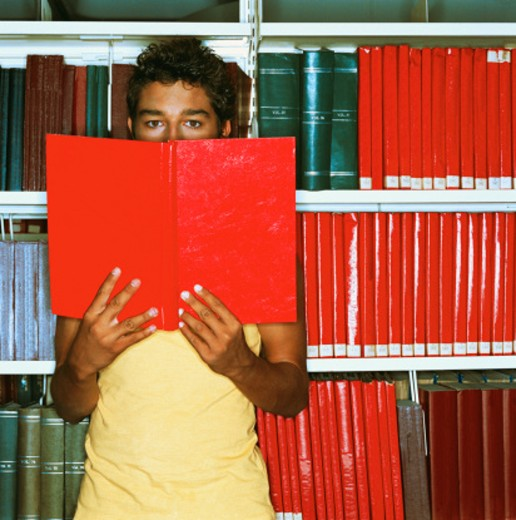 Stock Photo: 1491R-161080 view of a young man covering his face with a book in a library