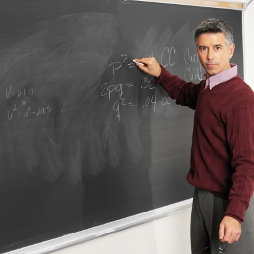 Stock Photo: 1491R-162357 Male teacher writing on a blackboard