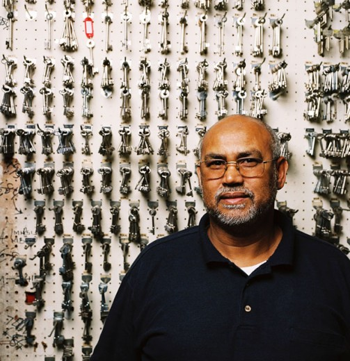 portrait of a key maker standing in front of an array of keys hung on a board : Stock Photo