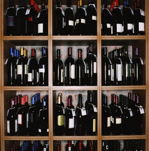 an array of wine bottles kept on display in shelves : Stock Photo
