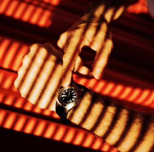 a man adjusting his wrist watch : Stock Photo