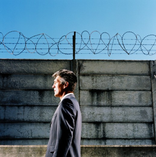 side profile of a businessman standing in a barbed enclosure : Stock Photo