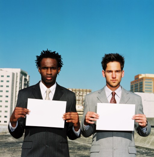 Stock Photo: 1491R-166022 portrait of two businessmen holding up blank sheets of paper