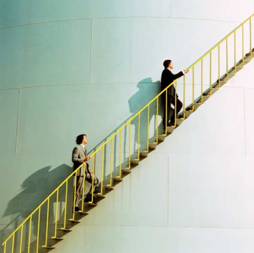 side profile of two businessmen climbing the ladder of an industrial silo : Stock Photo