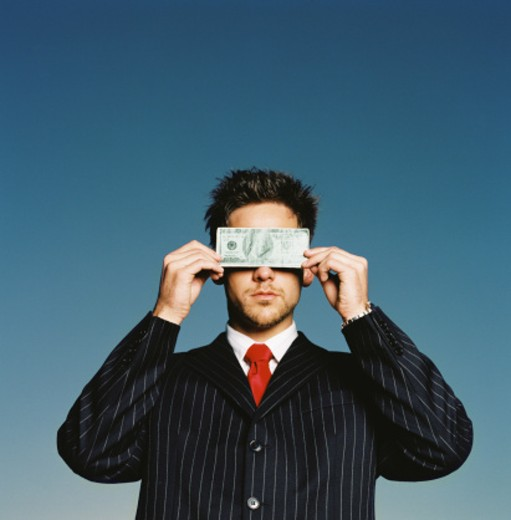 Stock Photo: 1491R-166101 a businessman covering his eyes with a currency note