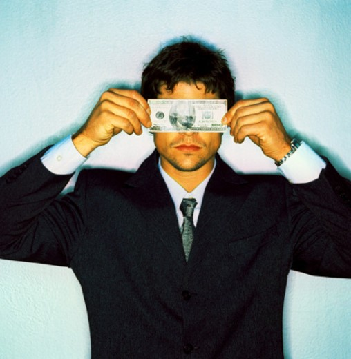 Stock Photo: 1491R-166102 a businessman covering his eyes with a currency note