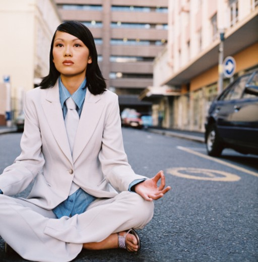 a businesswoman in a yoga pose sitting in the center of the street with eyes open : Stock Photo