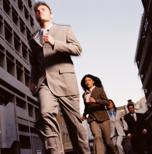 Stock Photo: 1491R-166146 low angle view of a group of men and women wearing business suits running on the street